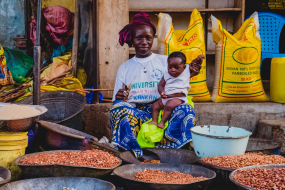 2 June 2015: women selling grains at the market while taking care of children, Kankan, Upper-Guinea, Republic of Guinea, West Africa