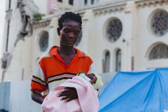 Earthquake survivor and Haitian mother holding her baby