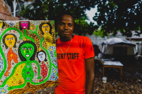 Haitian artist and earthquake survivor Sevenson Joseph holding one of his paintings in the courtyard of a partially destroyed art center, Jacmel, South-East Department, Haiti, Central America.